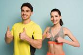 šťastný atletický pár stojící ve sportovním oblečení ukazující palce nahoru na modré