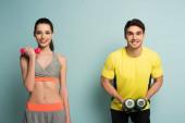 boldog atlétikai pár edzés súlyzókkal kék