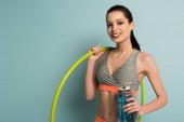 fröhliches athletisches Mädchen mit Hula-Hoop-Reifen und Sportflasche mit Wasser auf Blau