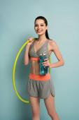 fröhliche athletische Frau mit Hula-Hoop-Reifen und Sportflasche mit Wasser auf Blau
