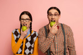 Photo couple of nerds in eyeglasses eating apples on pink