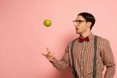 Photo shocked male nerd in eyeglasses throwing apple on pink
