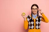 Photo smiling female nerd in eyeglasses holding apple on pink