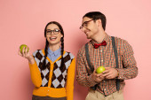 Photo couple of happy nerds in eyeglasses holding apples on pink