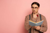 Photo thoughtful male nerd in eyeglasses reading book on pink