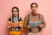 Photo couple of shocked nerds in eyeglasses reading books on pink