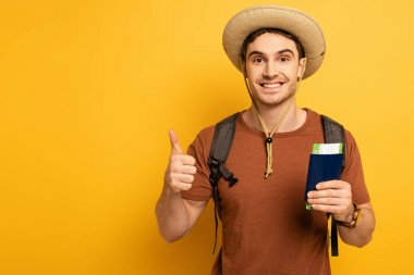 Cheerful tourist in hat with backpack holding passport and ticket while showing thumb up on yellow stock vector