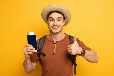 Handsome smiling tourist in hat with backpack holding passport and ticket while showing thumb up on yellow stock vector