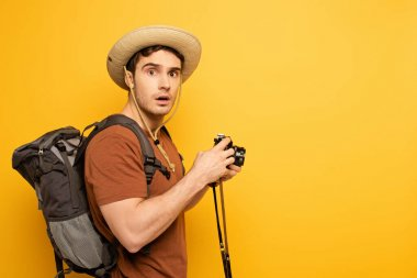 Shocked traveler in hat with backpack holding photo camera on yellow stock vector