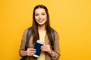 Smiling female tourist with backpack holding passport and ticket, isolated on yellow stock vector