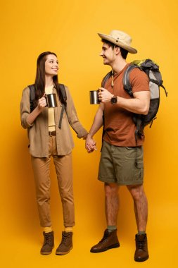 Couple of happy tourists with backpacks and cups of coffee holding hands on yellow stock vector