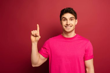 portrait of smiling man in pink t-shirt pointing up on red