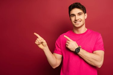 Portrait of smiling man in pink t-shirt pointing on red stock vector