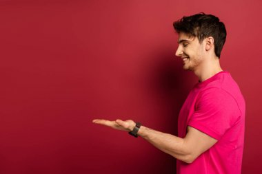 Portrait of smiling man in pink t-shirt presenting something on red stock vector