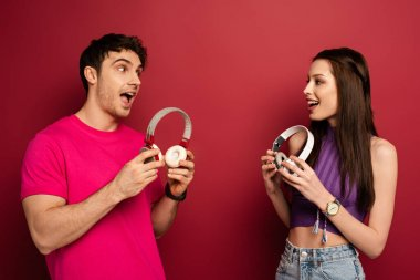 beautiful excited couple holding headphones on red
