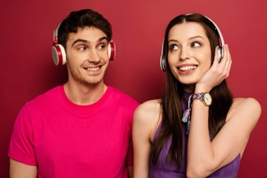 beautiful smiling couple listening music with headphones on red