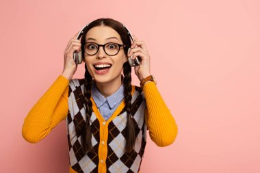excited female nerd in eyeglasses listening music with headphones on pink