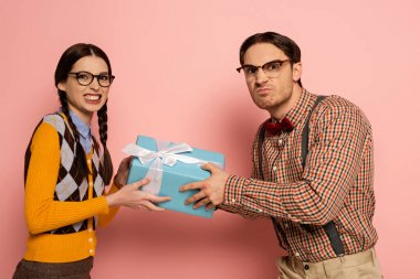 Couple of angry nerds in eyeglasses holding one gift on pink stock vector