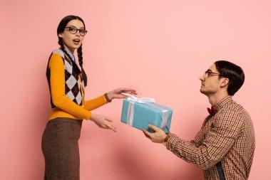 Handsome nerd giving present to surprised girlfriend on pink stock vector