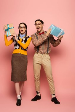 Couple of shocked nerds holding gift boxes on pink stock vector
