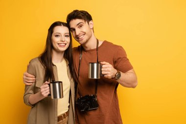 Couple of smiling tourists with photo camera holding cups with coffee on yellow stock vector