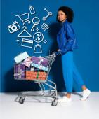 Fotografie Seitenansicht von glücklichen afrikanisch-amerikanischen Frau mit Einkaufswagen voller Geschenke auf blauem Hintergrund