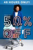 Fotografie lächelnde Afroamerikanerin mit Einkaufswagen voller Geschenke auf blauem Hintergrund, 50 Prozent Rabatt auf Online-Verkauf Illustration