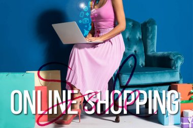 cropped view of african american woman sitting in velour armchair with laptop near gift boxes and purchases on blue background with online shopping illustration