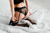 cropped view of sexy female dominant holding spanking paddle on bed