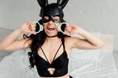 sexuelle weibliche Unterwürfigkeit in erotischer Kaninchenmaske beißt Handschellen im Bett
