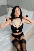 leidenschaftliche weibliche Dominanz in erotischen Dessous mit Peitsche im Schlafzimmer