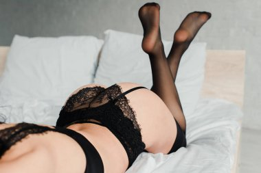 cropped view of sensual girl in black lingerie and stockings lying in bed