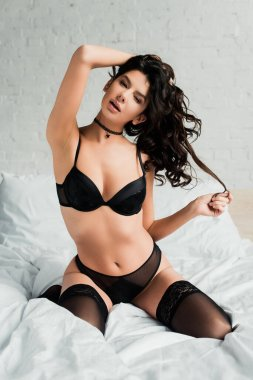 attractive sensual girl in black lingerie and stockings sitting on bed