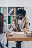 Ausgeschnittene Ansicht eines afrikanisch-amerikanischen Personalvermittlers beim Händeschütteln mit einem Mitarbeiter beim Vorstellungsgespräch im Büro
