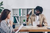 Selektiver Fokus eines afrikanisch-amerikanischen Personalvermittlers, der Stift in der Hand hält und Mitarbeiter mit Papieren am Tisch im Büro betrachtet