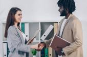 Afrikanisch-amerikanischer Angestellter und Personalvermittler mit Dokumenten, die einander anschauen, lächelnd und Hände schüttelnd im Büro