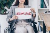 Fotografie Ausgeschnittene Ansicht eines behinderten Mitarbeiters mit Plakat mit arbeitslosem Schriftzug am Rollstuhl im Büro