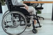 Teilansicht eines behinderten Mitarbeiters im Rollstuhl am Tisch im Büro