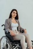 Behinderte Frau blickt auf Kamera im Rollstuhl isoliert auf weiß