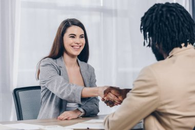 Selective focus of employee smiling and shaking hands with african american recruiter at job interview in office stock vector