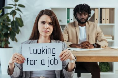 Worried employee showing placard with looking for a job lettering and african american recruiter in office