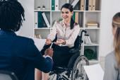 Az afro-amerikai toborzó szelektív fókusza, aki papírt és tollat ad az irodai fogyatékkal élő alkalmazottaknak