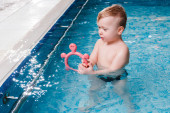 Photo cute toddler kid playing with rubber toy in swimming pool