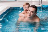 šťastný batole dítě a trenér plavání se usmívá v bazénu