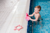 Photo happy toddler kid playing with rubber duck in swimming pool