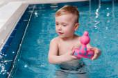 roztomilé batole chlapec hrát s gumovou hračkou v bazénu