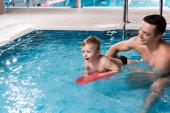 plavání trenér výuka šťastný batole dítě s flutter palubě v bazénu