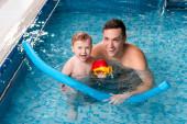 pohledný plavecký trenér úsměv s batole chlapec v bazénu