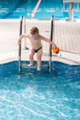 roztomilý batole chlapec s hračkou lezení bazén žebřík