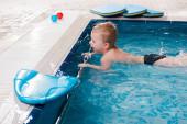 šťastný batole chlapec plavání v blízkosti flutter desky v bazénu